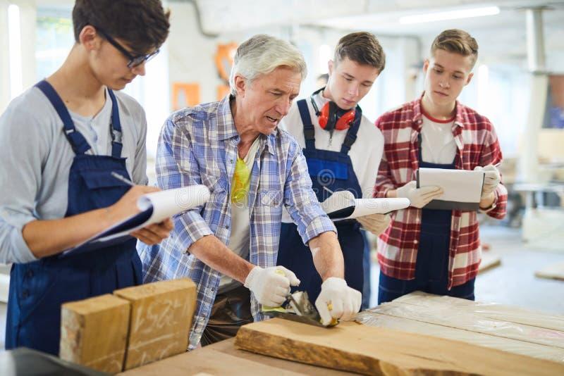 Professional carpenter explaining how to make wooden plank smoot stock image