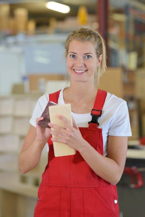 Professional carpenter woman sanding wood. Woman royalty free stock photo