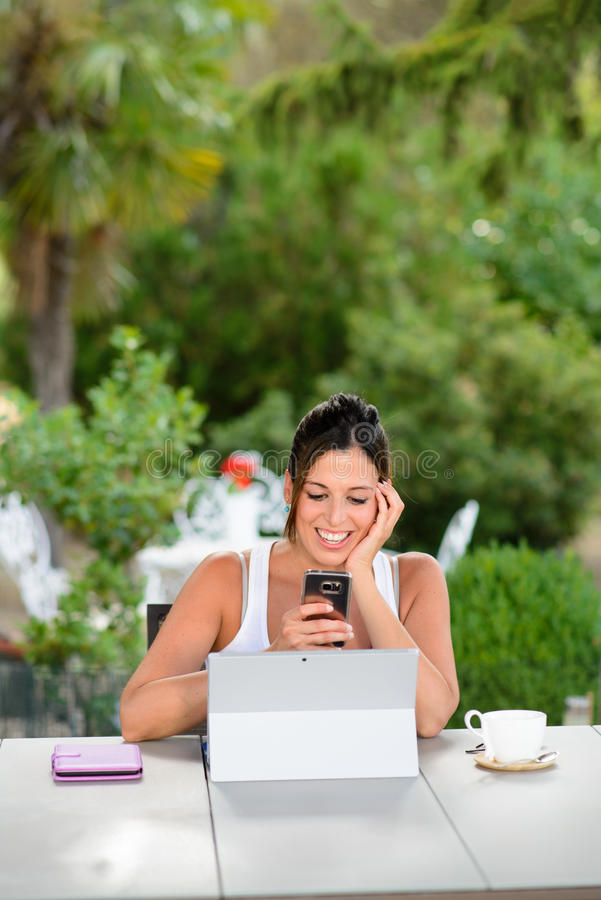 Professional casual woman with laptop and smartphone outside stock photography