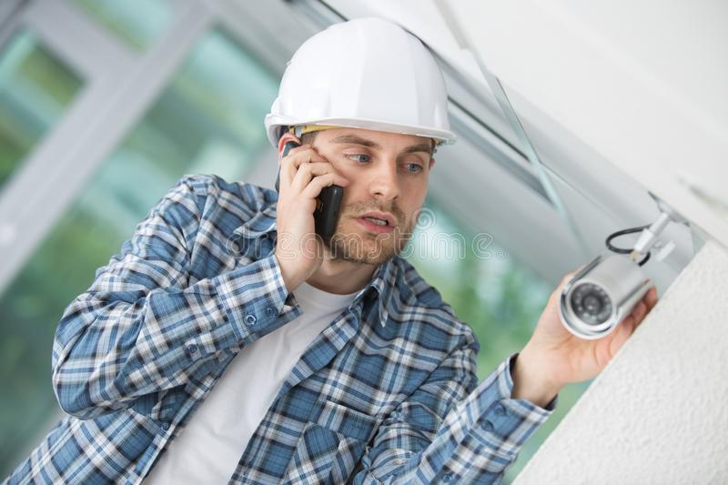 Professional cctv technician installing device stock images