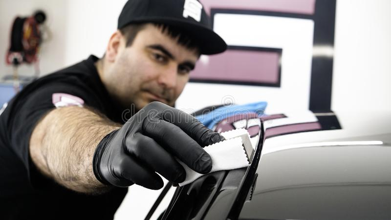Professional ceramics handler apply different layers to the car using an applicator sponge, fiber immediately checking the effec. T. Concept from: Autodetailing royalty free stock image