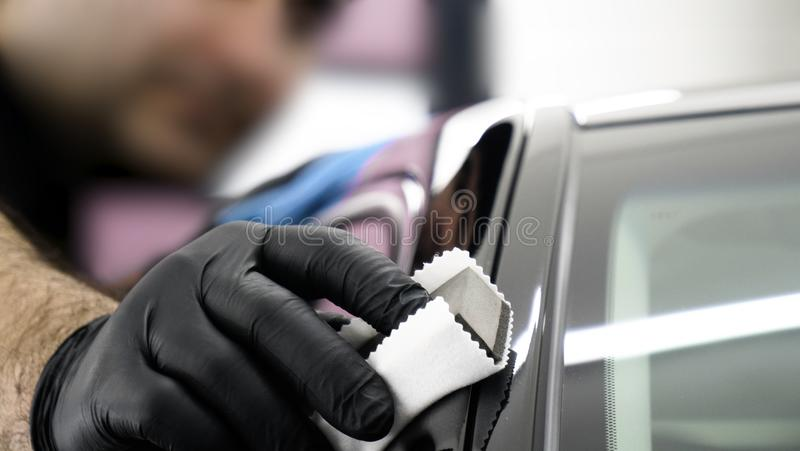 Professional ceramics handler apply different layers to the car using an applicator sponge, fiber immediately checking the effec. T. Concept from: Autodetailing stock photography