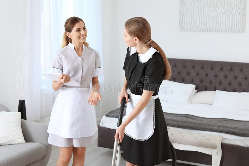 Professional chambermaid in uniform teaching trainee. Indoors royalty free stock photography
