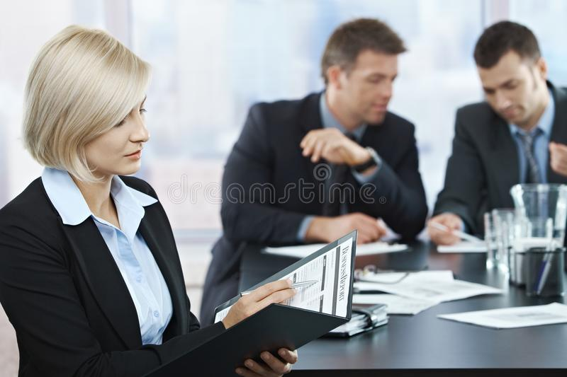 Professional checking documents at meeting. Professional businesswoman checking documents at business meeting with coworkers in background stock photos