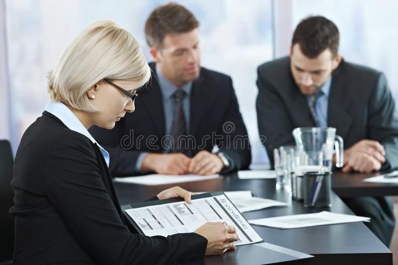 Professional checking documents at meeting. Professional businesswoman checking documents at business meeting with coworkers in background stock photography