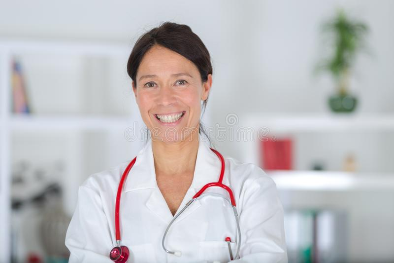 Professional and cheerful female doctor in white coat stock images