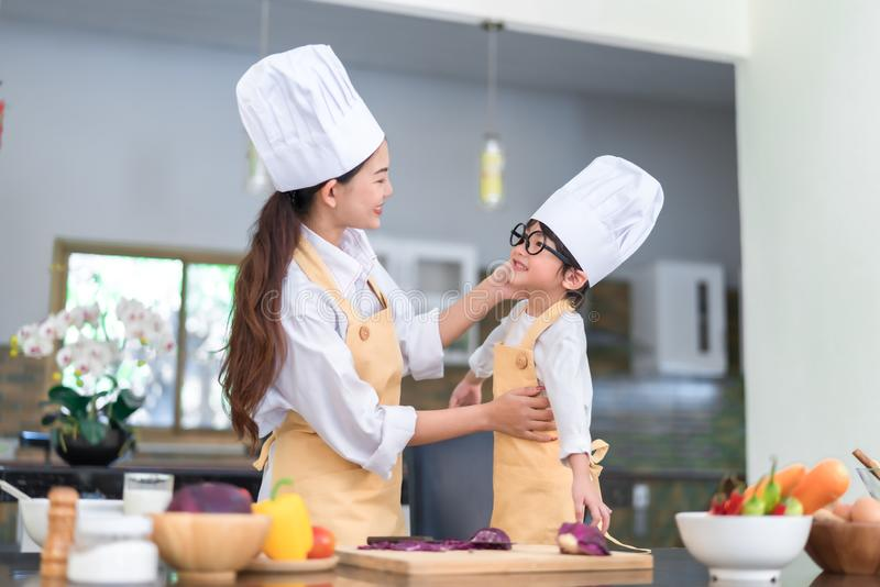 Professional Chef asian mom dressed up little son ready teaching cooking salad. Vegetable knowledge prepare healthy food in the kitchen room stock images