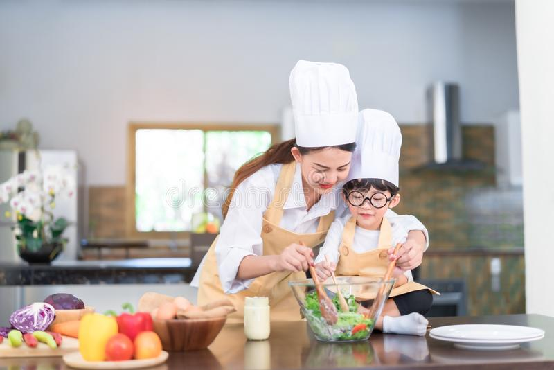 Professional Chef asian mom teaching little son cooking. Salad vegetable prepare healthy food in the kitchen room for dinner at home happy family lifestyle stock photos