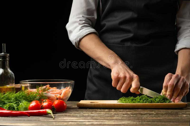 Professional chef cuts greens for salad with shrimps, the concept of seafood and healthy food. Horizontal photo, menu, recipe book stock image