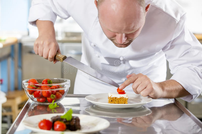 Professional chef decorates dessert cake with strawberry in kitchen royalty free stock photography