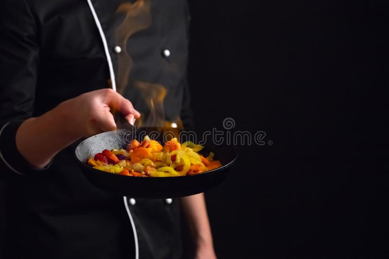 Professional chef and fire. Cooking vegetables and food over an open fire on a dark background. Hotel service photo background. Wi. Th copy space for your text stock photography