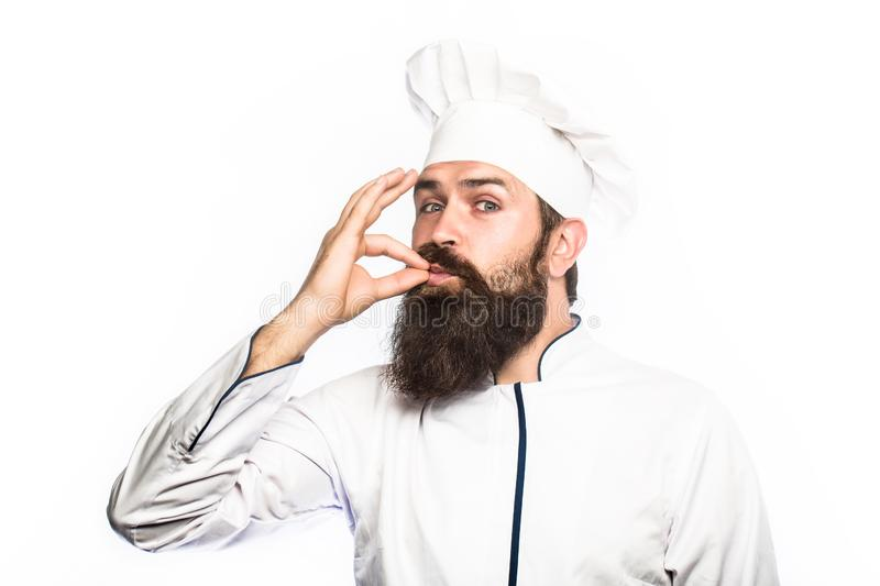 Professional chef man showing sign for delicious. Chef, cook making tasty delicious gesture by kissing fingers. Cook hat stock photography
