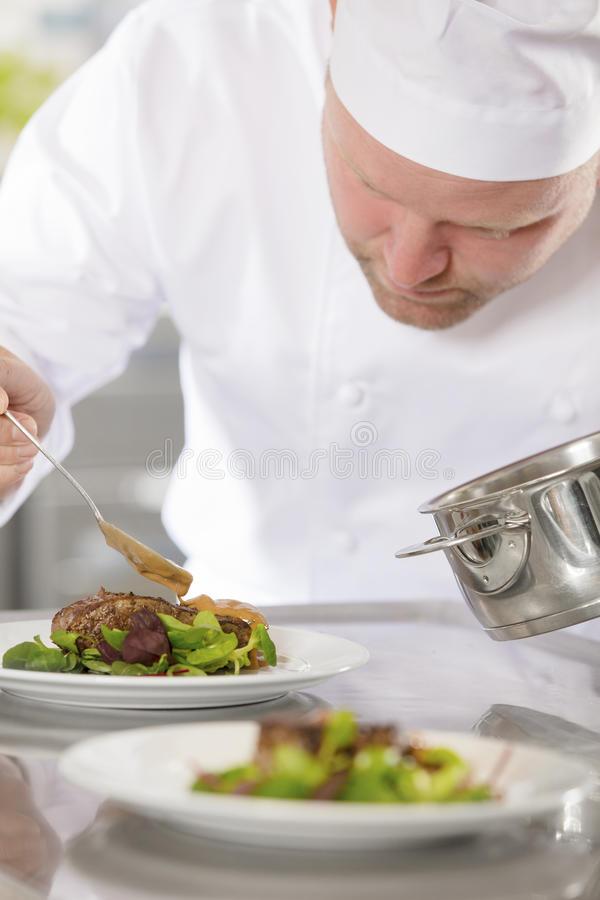 Professional chef prepare meat dish at restaurant stock photo