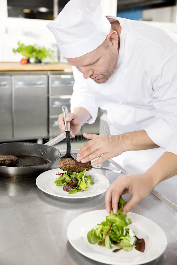 Professional chef prepare steak dish at restaurant. Chef and his assistant prepare meat dish in a professional kitchen at restaurant or hotel royalty free stock images