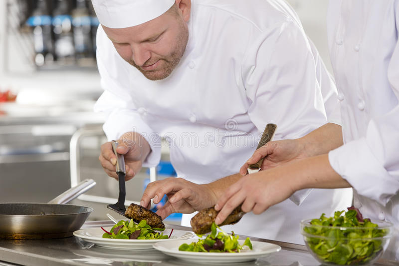 Professional chef prepare steak dish at restaurant. Smiling chef and his assistant prepare meat dish in a professional kitchen at restaurant or hotel royalty free stock photo