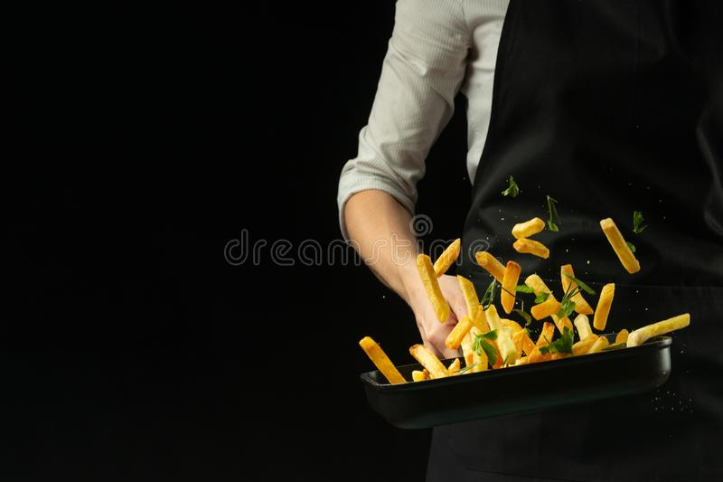 Professional chef prepares french fries with greens. Horizontal view stock images