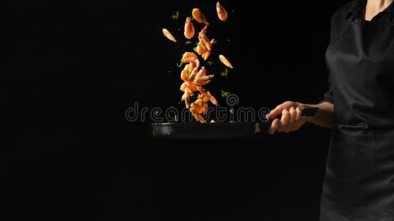 Professional chef prepares shrimps with greens. Cooking seafood, healthy vegetarian food, and food on a dark background. Horizonta stock images
