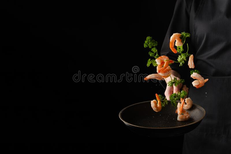 Professional chef prepares shrimps with greens. Cooking seafood, healthy vegetarian food, and food on a dark background. royalty free stock image