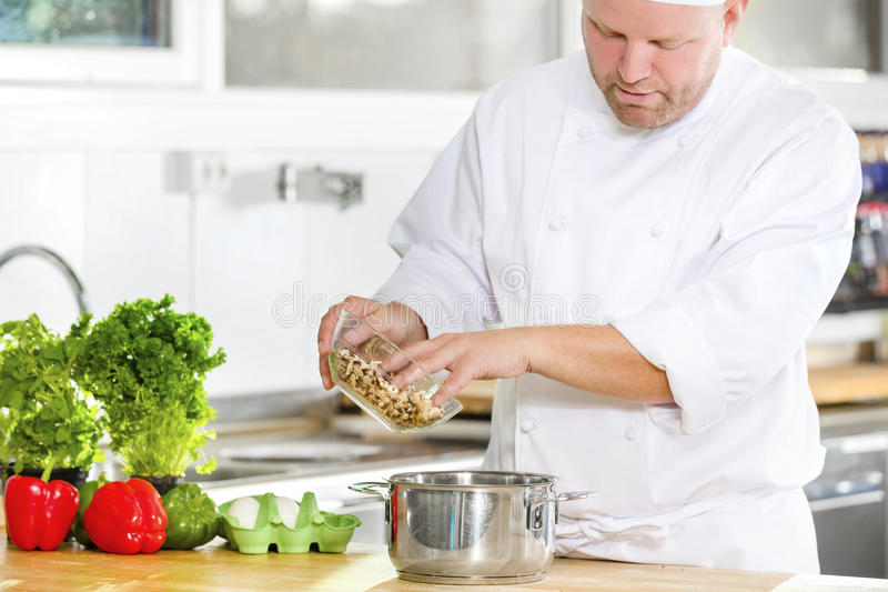 Professional chef preparing food in large kitchen royalty free stock photography