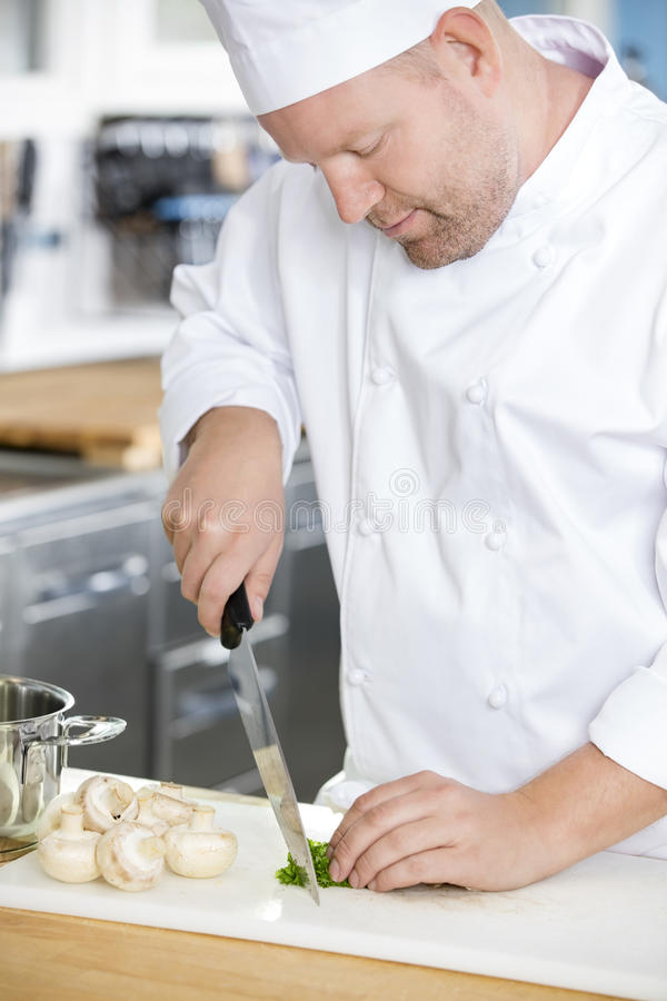 Professional chef preparing vegetables to a healthy dish royalty free stock photo