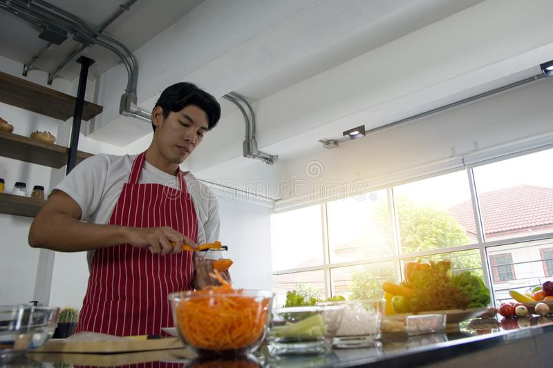 The professional chef with rough hands to grate carrots to prepare cookinging for breakfast. In home kitchen stock images