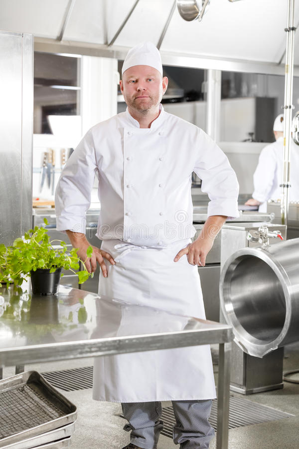 Professional chef standing in large kitchen. Portrait of a confindent and smiling male chef standing in the large kitchen with his hands on the hips. Assistant stock photos