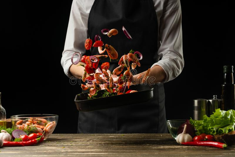 Professional chef threw shrimps with vegetables on the grill pan, freezing in motion, concept of seafood and healthy food. royalty free stock photos