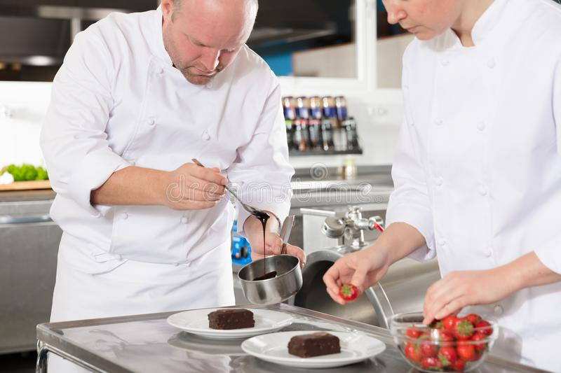 Professional chefs decorate dessert cake with lemon leaf stock images