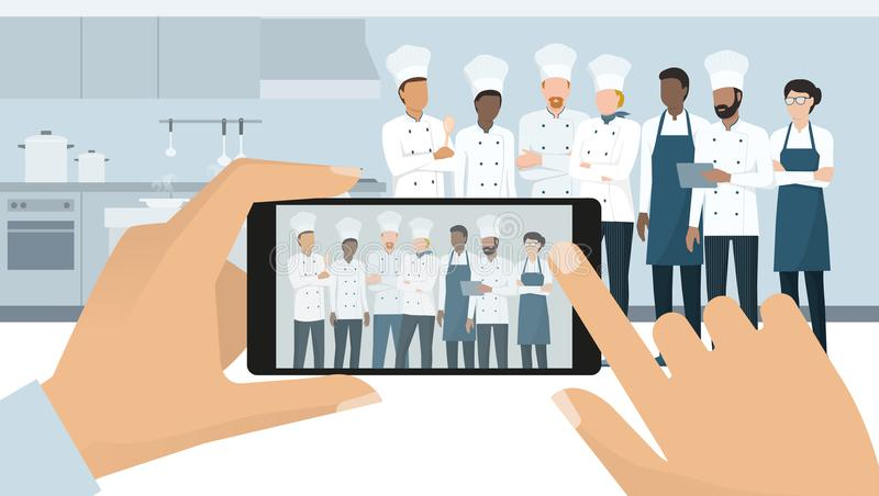 Professional chefs posing in the restaurant kitchen. A man is taking a picture using a smartphone, subjective point of view royalty free illustration