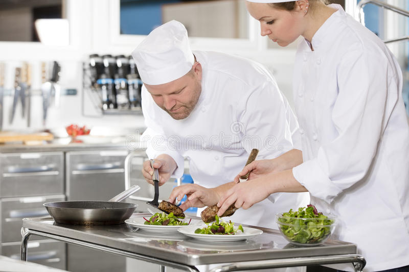 Professional chefs prepare steak dish at restaurant. Two chefs prepare meat dish in a professional kitchen at restaurant or hotel royalty free stock image