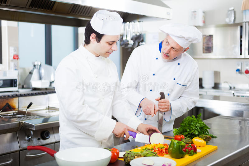 Professional chefs at work. Chief chef watching his assistant garnishing a dish stock photos