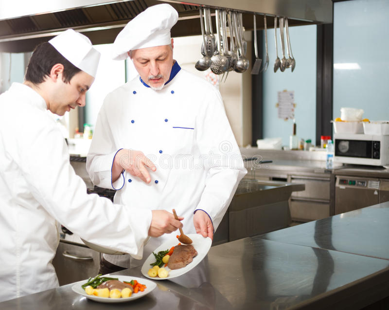 Professional chefs at work. Chief chef watching his assistant garnishing a dish royalty free stock photos