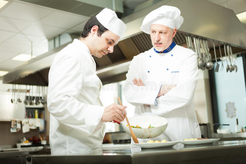 Professional chefs at work. Chief chef watching his assistant garnishing a dish royalty free stock photo