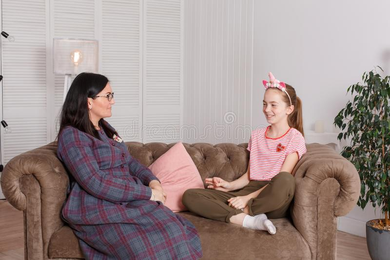 Professional child psychologist with a teenage girl. Teen girl tells a story with a smile on her face. The method of work of a. Child psychotherapist royalty free stock images