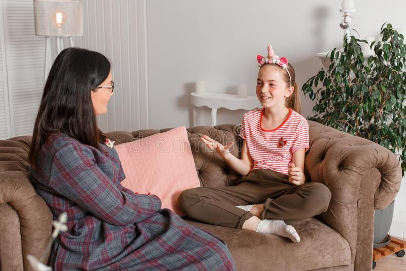Professional child psychologist with a teenage girl. A teenage girl tells a story emotionally waving her arms. The method of work stock photos