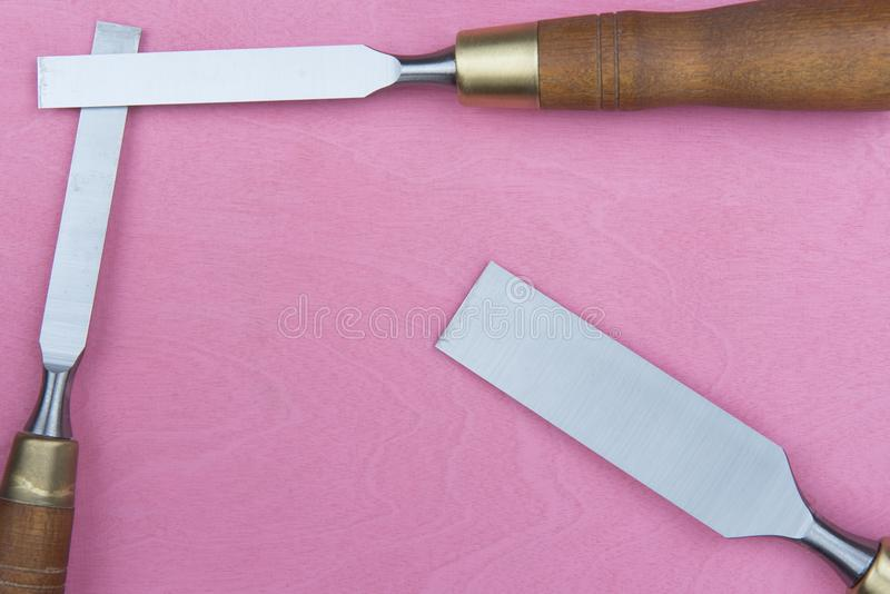 Three Chisels on a pink background. Professional chisels on a pink wood background. Visible wood grain royalty free stock photo