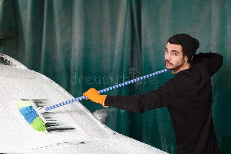 A professional cleaner washes a car stock photo