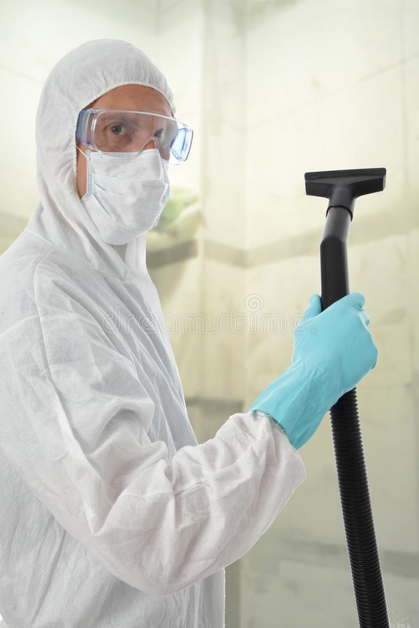Professional cleaner in protective suit. With safety goggles and mask about to commense work with his vacuum to clean the interior of a building stock images