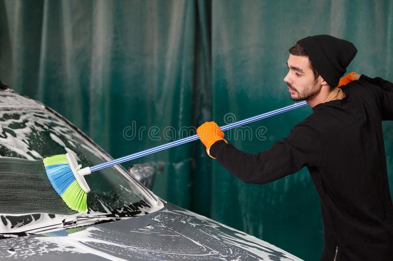 A professional cleaner washes a car royalty free stock photography