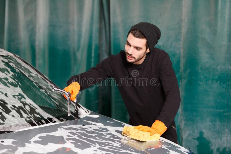A professional cleaner washes a grey car royalty free stock photo