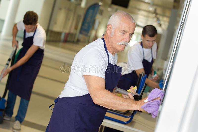 Professional cleaners team in uniform working royalty free stock photos