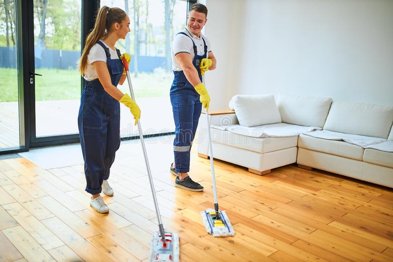 Professional cleaners team working in living room stock image