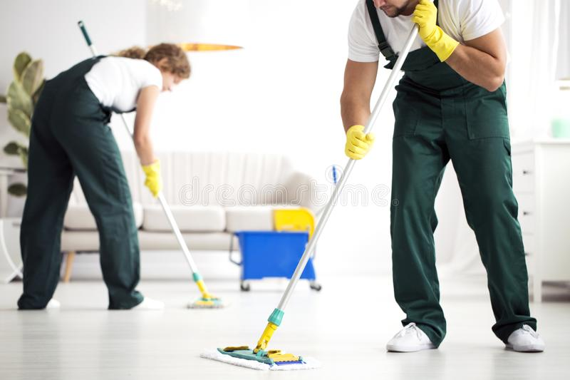 Professional cleaning crew washing floor stock photography