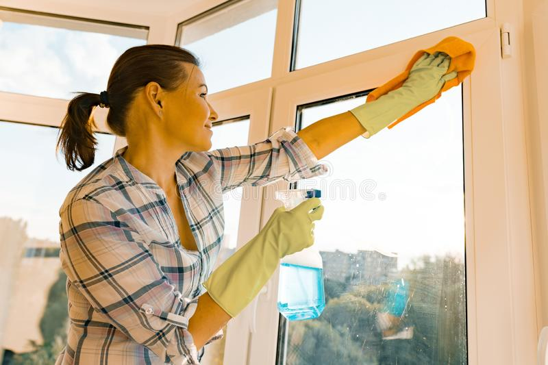 Professional cleaning service. Woman housekeeper cleaning windows stock images