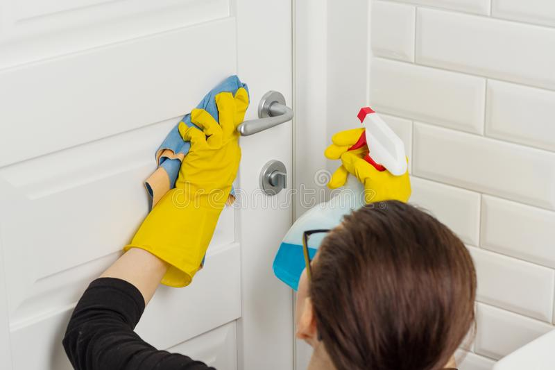 Professional cleaning services. Woman worker in rubber gloves doing cleaning in the bathroom, cleaning door with rag and detergent royalty free stock image