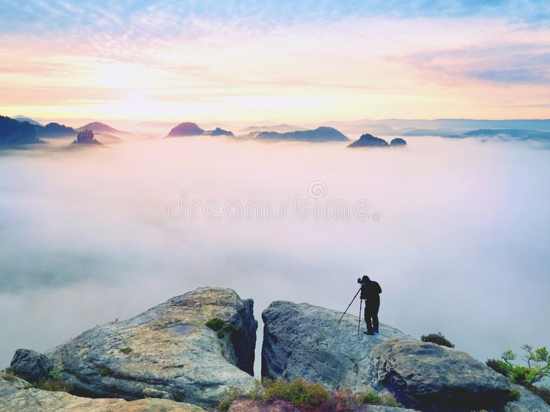 Professional on cliff. Nature photographer takes photos with mirror camera on peak of rock. Dreamy fog. Professional on cliff. Nature photographer takes photos stock photos