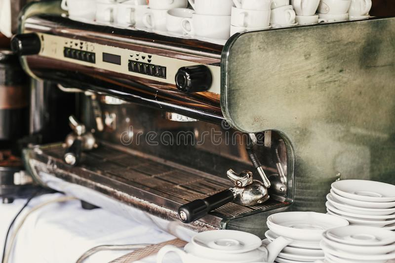 Professional coffee machine in cafe. Big steel and white coffee machine and ceramic cups and plates on table in cafe or wedding. Reception. Luxury catering stock image