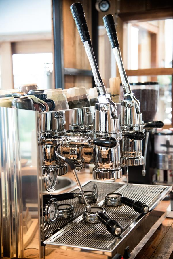 Professional coffee machine closeup with selective focus at modern coffee shop counter bar. Vintage coffee shop royalty free stock image