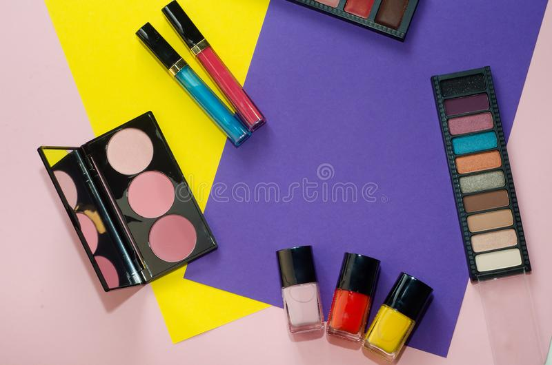 Professional colorful makeup tools, flatlay on pink, yellow and violet background. Palette eyeshadow, blush, lipstick stock photography