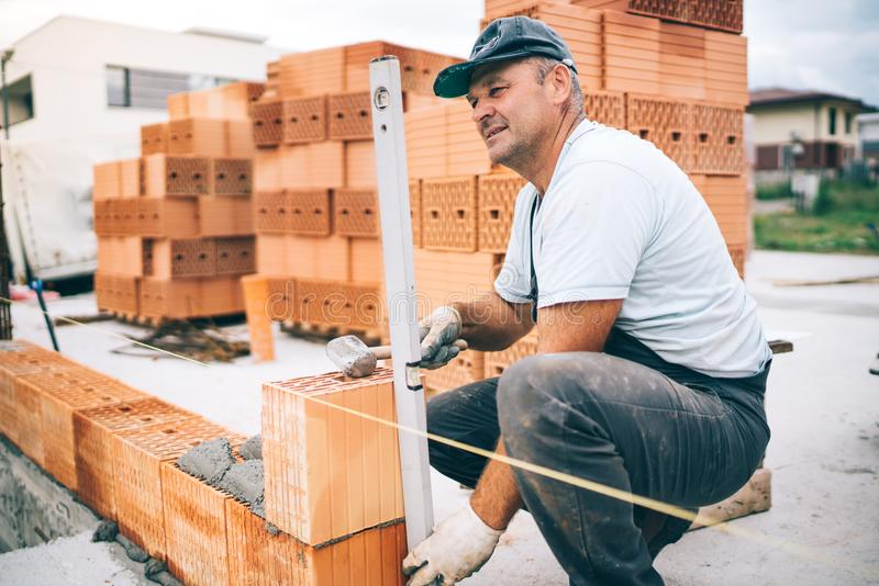 Professional construction worker laying bricks and building house in industrial site. Detail of hand adjusting bricks stock photos